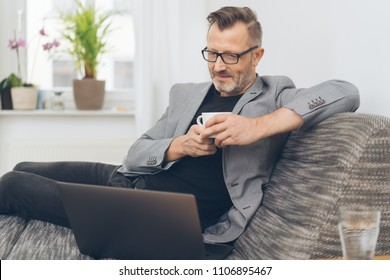 Portrait of mature man having coffee while sitting on sofa with laptop