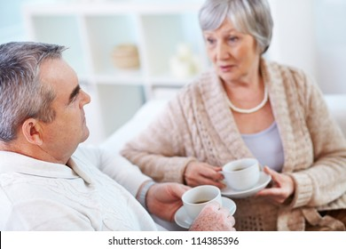 Portrait of mature man and his wife drinking tea and interacting