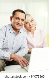 Portrait of mature man and his wife with laptop looking at camera