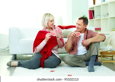 Portrait of mature man and his wife playing cards at home
