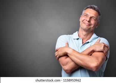 Portrait Of A Mature Man Hugging Himself Against Grey Background