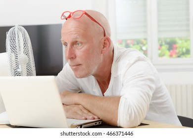 portrait of mature man with a laptop in the house