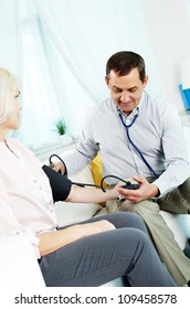 Portrait of mature man measuring blood pressure of his wife