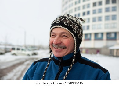 Portrait of mature man outdoors in winter. He is standing outdoor on street and smiles