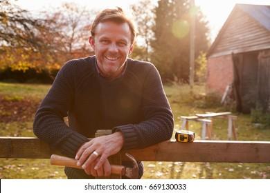 Portrait Of Mature Man Repairing Garden Fence