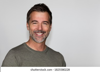 Portrait Of A Mature Man Smiling At The Camera. Isolated on white. Left side.