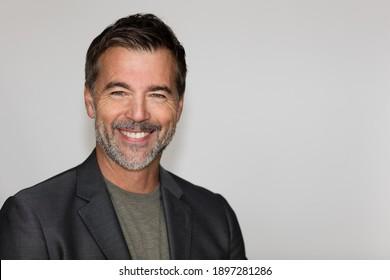 Portrait eines reife Mannes, der die Kamera lächelt. Einzeln auf Weiß. Links. Jacquet