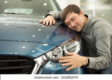 Portrait of a mature man smiling joyfully embracing a new car at the dealership showroom copyspace love driving masculine hobby transport technology modern vehicle buying sales consumerism shopping.
