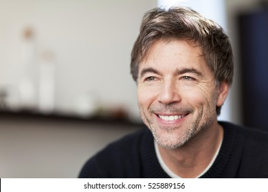 Portrait Of A Mature Man Smiling And Looking Away. Home.