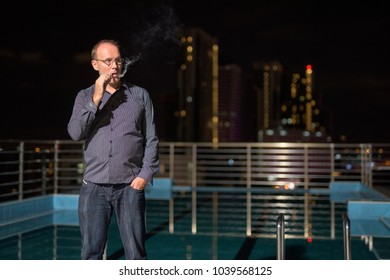 Portrait of mature man smoking electronic cigarette on the rooftop swimming pool