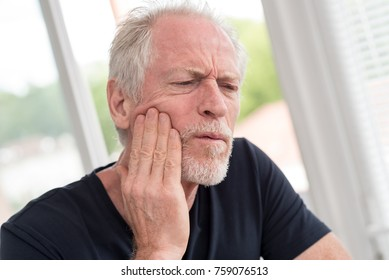 Portrait of mature man with toothache at home