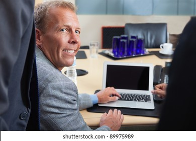 Portrait of mature man using laptop in office