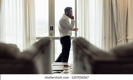 Portrait of mature man walking inside a hotel room and talking on phone. Businessman making phonecall from hotel room on business trip.