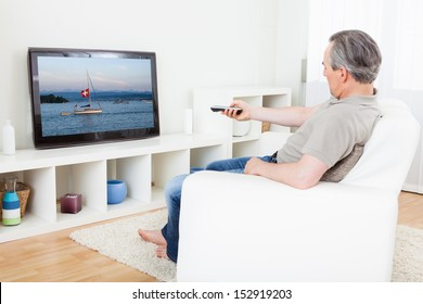 Portrait of a mature man watching tv at home