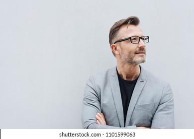 Portret van volwassen man dragen grijs jasje staande tegen witte muur met kopie ruimte