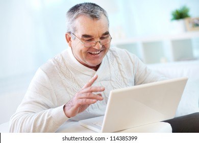 Portrait of mature man working with laptop at home