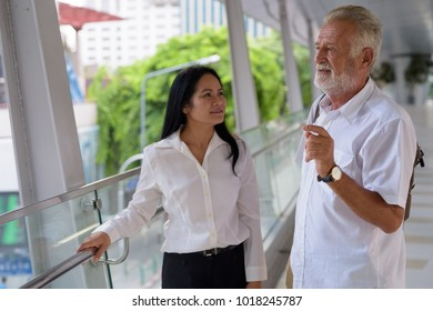Portrait of mature multi-ethnic couple on the footbridge against view of the city in Bangkok, Thailand