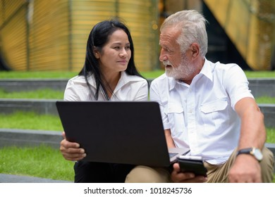 Portrait of mature multi-ethnic couple relaxing outside the building in Bangkok, Thailand