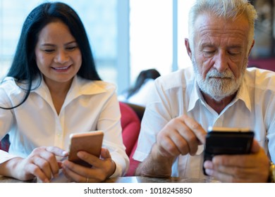 Portrait of mature multi-ethnic couple relaxing together inside the coffee shop in Bangkok, Thailand