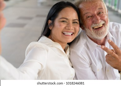 Portrait of mature multi-ethnic couple at the skytrain station in Bangkok, Thailand