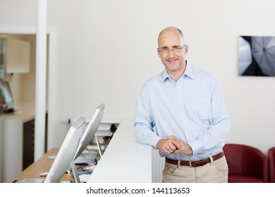 Portrait of mature patient leaning on reception at dentist's clinic