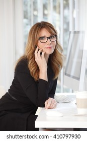 Portrait of mature professional woman talking on mobile phone while sitting at office in front of computer.