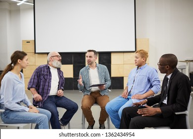 Portrait of mature psychologist leading therapy session in support group, copy space