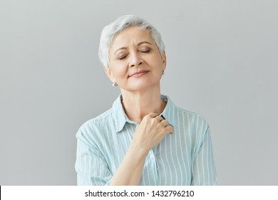 Portrait of mature retired European woman keeping eyes closed, listening to calm relaxing music, having pleased joyful look, daydreaming or reminiscing. Human facial expressions, emotions and reaction