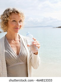 Portrait of a mature smiling beautiful woman on beach destination drinking mineral water, on shore of inviting blue sea, aspirational travel lifestyle, sunny outdoors nature.