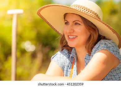 Portrait of mature smiling woman wearing big straw hat in garden