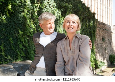 Portrait of mature tourist couple relaxing sightseeing monument on vacation trip, smiling looking outdoors. Senior man and woman enjoying city break travel together, leisure recreation lifestyle.