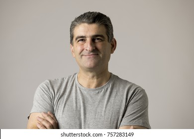 portrait of mature white man 40 to 50 years old smiling happy showing nice and positive face expression with folded crossed arms isolated on grey background in feelings and emotions concept