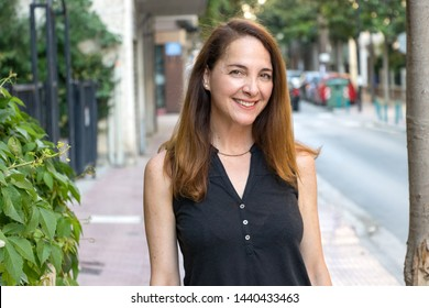 Portrait of a mature woman, 40s, smiling looking camera outdoors in a city.