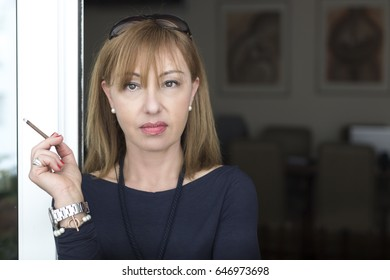 Portrait of a mature woman, 45 years old, holding a cigarette looking at camera, home background.