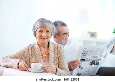 Portrait of mature woman with cup of tea looking at camera on background of her husband reading newspaper