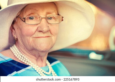 portrait of a mature woman in glasses and hat sitting in car .