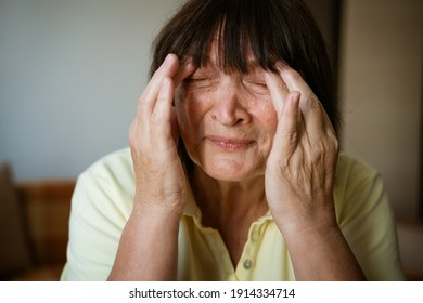 Portrait of a mature woman holding her head with her hands for headache