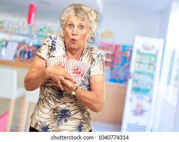 Portrait Of Mature Woman Holding Popcorn, Indoors
