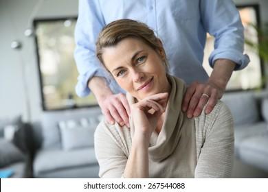 Portrait of mature woman, husband's hands on shoulders