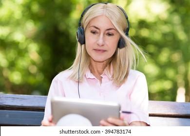 Portrait of a mature woman listening music outdoors