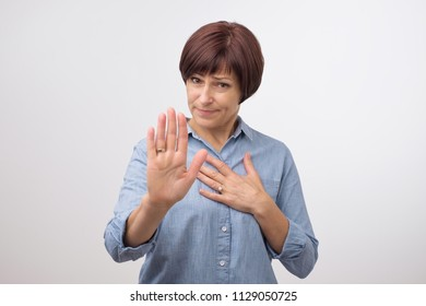 Portrait of mature woman making stop sign with her hand. She is refusing to accept news.