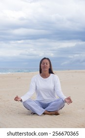 Portrait mature woman meditating at beach with closed eyes concentrated and relaxed, laid back, with ocean and cloudy sky as blurred background and copy space.
