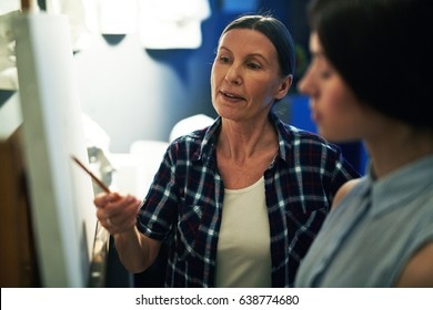 Portrait of mature woman professor helping student to draw, discussing work and explaining mistakes