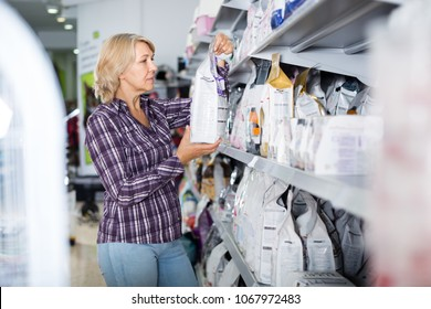 Portrait of mature woman purchasing pet food in petshop
