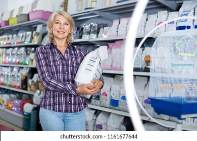 Portrait of mature woman purchasing pet food in petshop