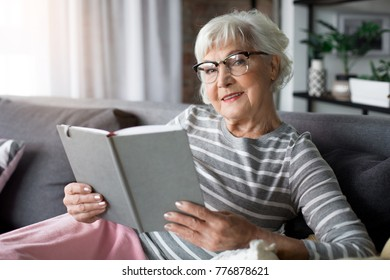 Portrait of mature woman resting at living room. She is reading novel and smiling
