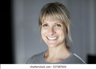 Portrait Of A Mature Woman Smiling At The Camera. At Home