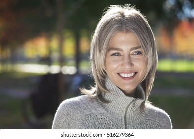 Portrait Of A Mature Woman Smiling And Looking Away. Outside.