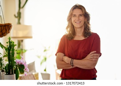 Portrait of a mature woman smiling while standing with her arms crossed in her sunny home