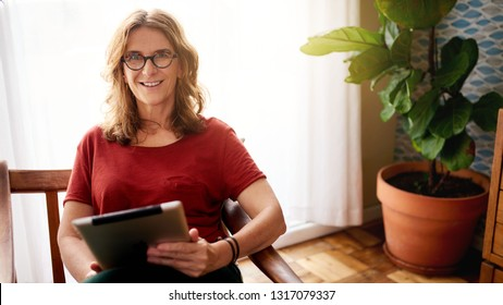 Portrait of a mature woman smiling while sitting in a chair in her sunny home browsing the internet with a digital tablet